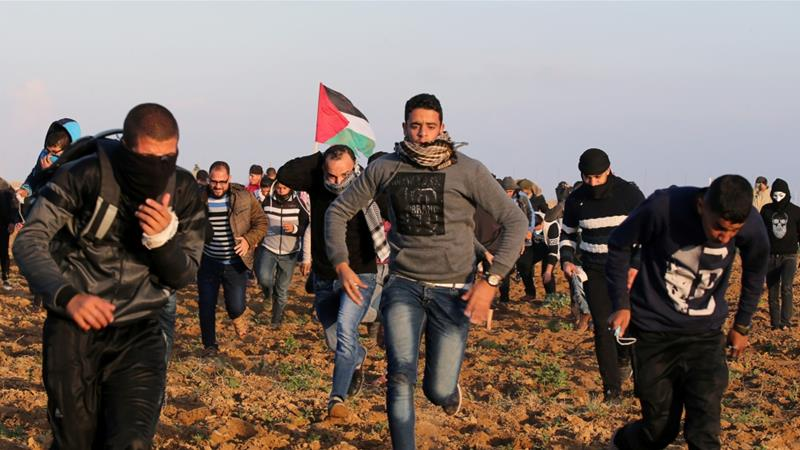 Palestinian demonstrators run for cover from Israeli gunfire and tear gas during a protest in the Gaza Strip [Ibraheem Abu Mustafa/Reuters]