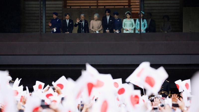 Akihito, flanked by members of the imperial family on a balcony, addressed well-wishers waving small Japanese flags [IIssei Kato/Reuters]