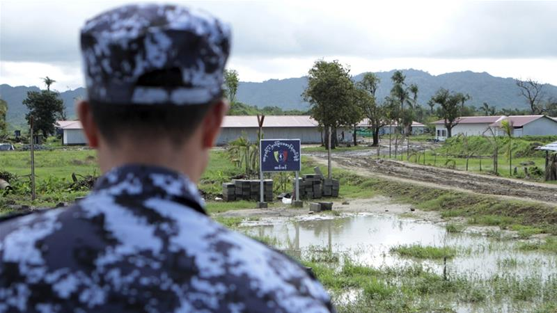 In this file photo from June, a police officer stands watch in Inndin village in Rakhine State [Min Kyi Thein/AP Photo]