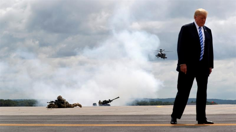 US President Donald Trump observes a demonstration with US Army 10th Mountain Division troops, a helicopter and artillery as he visits Fort Drum, New York, August 13 [File: Carlos Barria/Reuters]