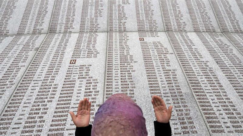 A Bosnian-Muslim woman prays at a memorial wall with the names of the Srebrenica victims [Elvis Barukcic/AFP/Getty Images]