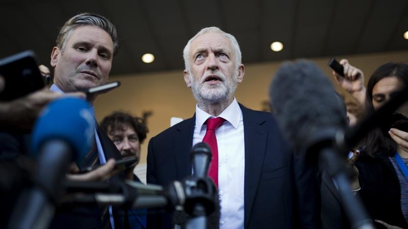 Keir Starmer (left) and Labour leader Jeremy Corbyn (centre) are set to submit a no confidence motion if May's Brexit plan fails to pass a December 11 parliamentary vote [File: Francisco Seco/AP]