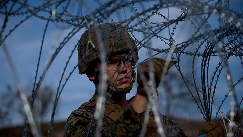 A soldier sets up barbed wire at the San Ysidro port of entry, at the US-Mexico border [File: Ramon Espinosa/AP Photo]