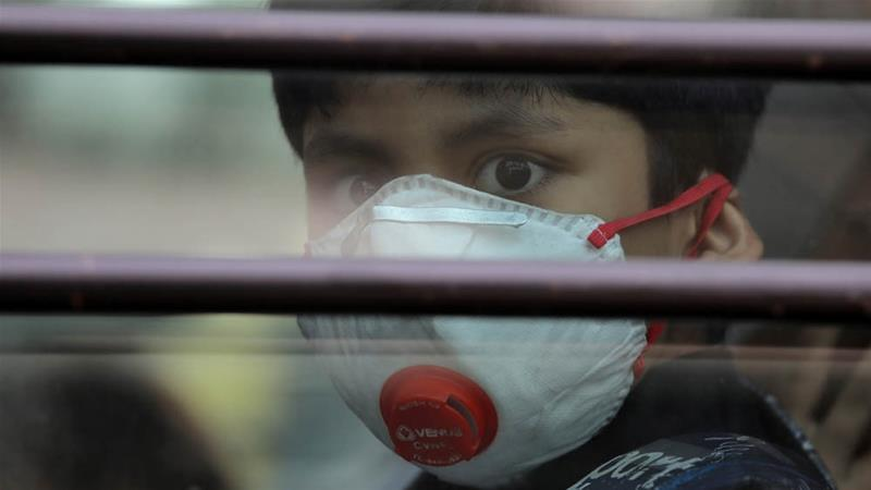A schoolboy wearing a protective mask in Ghaziabad on the outskirts of New Delhi [Anushree Fadnavis/Reuters]