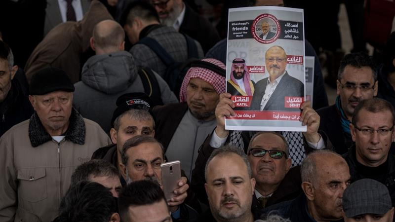 A man holds a poster showing Jamal Khashoggi after taking part in an funeral prayer in Istanbul [Chris McGrath/Getty Images]