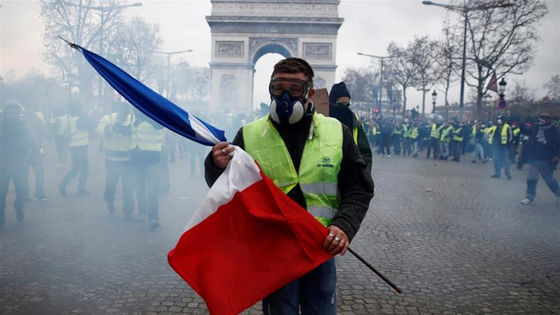 A protester wearing a yellow vest holds a French flag as he walks through tear gas on the Champs-Elysees Avenue in Paris, France [Christian Hartmann/Reuters]