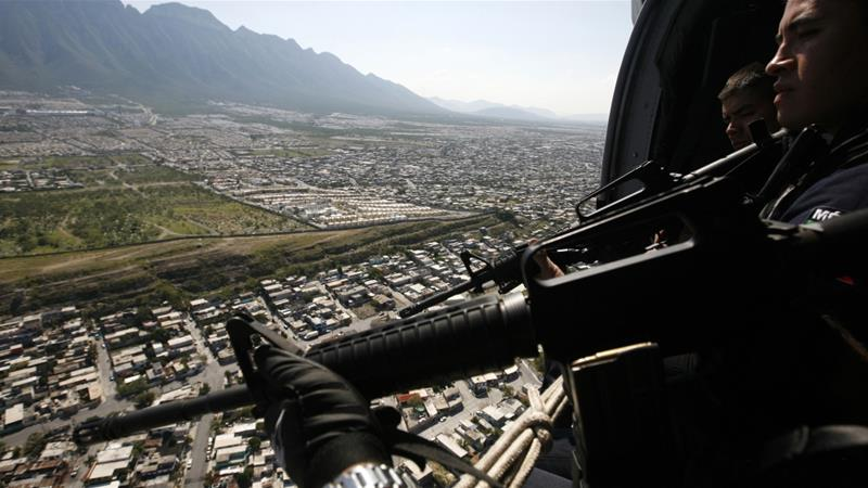Federal police officers hold their weapons while patrolling the city of Monterrey, Mexico [Carlos Jasso/Reuters]