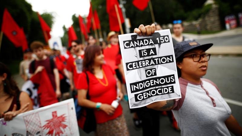 An indigenous rights activist holds a protest sign during Canada's 150th anniversary in Toronto, Ontario [File: Mark Blinch/Reuters]