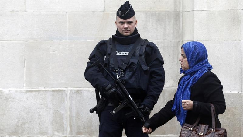 Police stands guard as a Muslim woman leaves the Great Mosque of Paris [File photo/Thierry Chesnot/Getty Images]