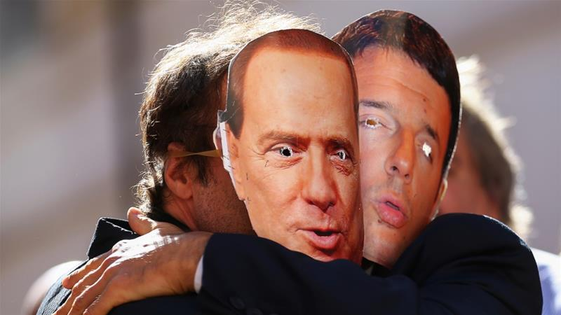 5-Star Movement supporters wear masks depicting former Italian Prime Ministers Silvio Berlusconi and Matteo Renzi during a protest in Rome, Italy [Alessandro Bianchi/Reuters]