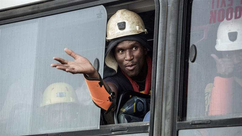 A rescued miner gestures out a bus window carrying some of the hundreds of miners rescued from the shaft [Gianluigi Guercia/AFP]