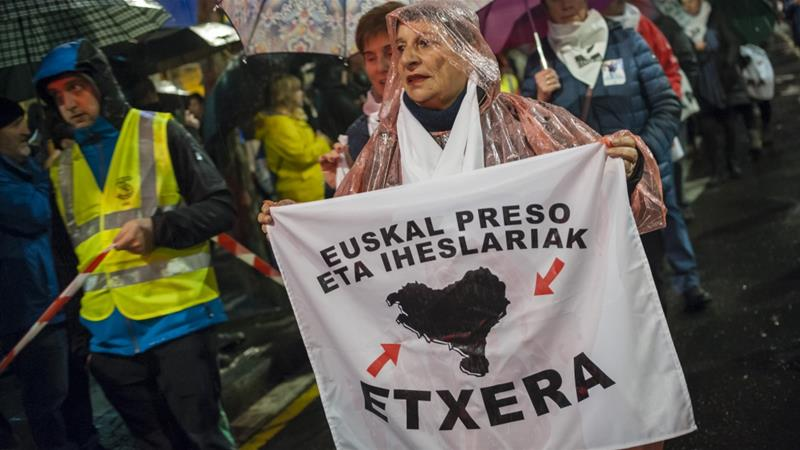 A Basque woman holds a banner with the Basque country at a protest for ETA prisoners's visitation rights [Gari Garaialde/Getty Images)