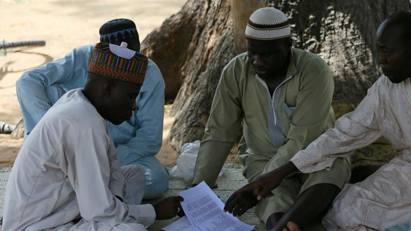 Parents of missing school girls check name lists in Dapchi in the northeastern state of Yobe, after an attack on the village by Boko Haram, Nigeria February 23, 2018.[Photo//Afolabi Sotunde/Reuters]