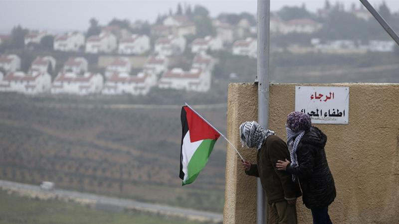 A protester holds the Palestinian flag with the Jewish settlement of Halamish seen in the background [Mohamad Torokman/Reuters]
