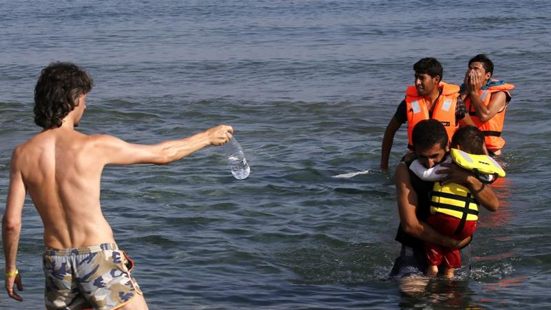 A tourist offers water to migrants as they arrive by paddling an engineless dinghy from the Turkish coast at a beach on the Greek island of Kos [Yannis Behrakis/Reuters]