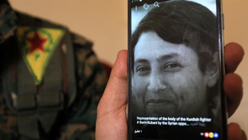 A military commander of the Syrian Kurdish Women's Protection Units, displays a picture of late 23-year-old YPJ fighter Barin Kobani [File: Delil souleiman/AFP]