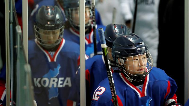 The inter-Korea's women's ice hockey players walk onto the ice on Sunday