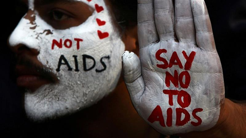 A student displays his face and hand painted with messages during an HIV/AIDS awareness campaign on the occasion of World AIDS Day in Chandigarh, India. [File: Ajay Verma/Reuters]