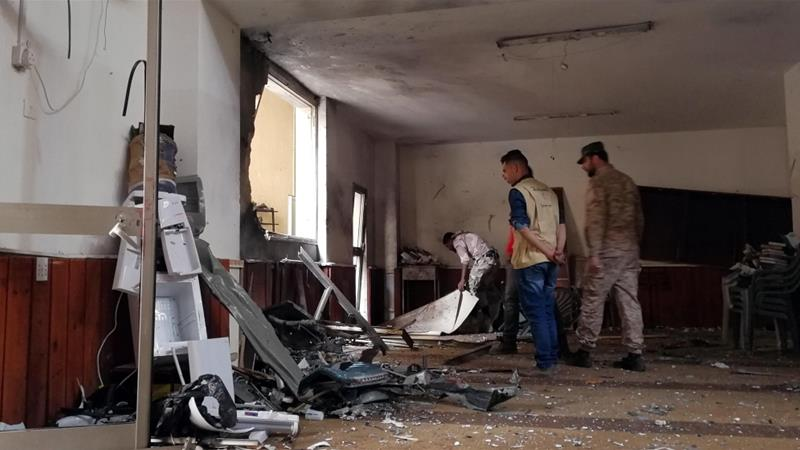 People inspect the damage inside the mosque in Benghazi