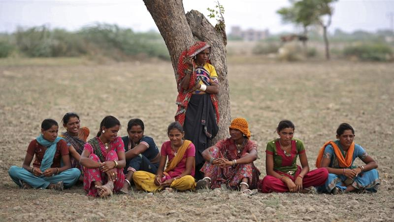 Village women rest under a tree as they migrate due to shortage of water in the western Indian state of Gujarat in August, 2012 [Ahmad Masood/Reuters]