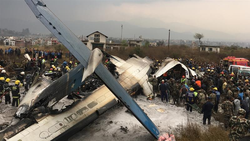 Nepalese rescuers stand near a passenger plane from Bangladesh that crashed at the airport in Kathmandu [AP]