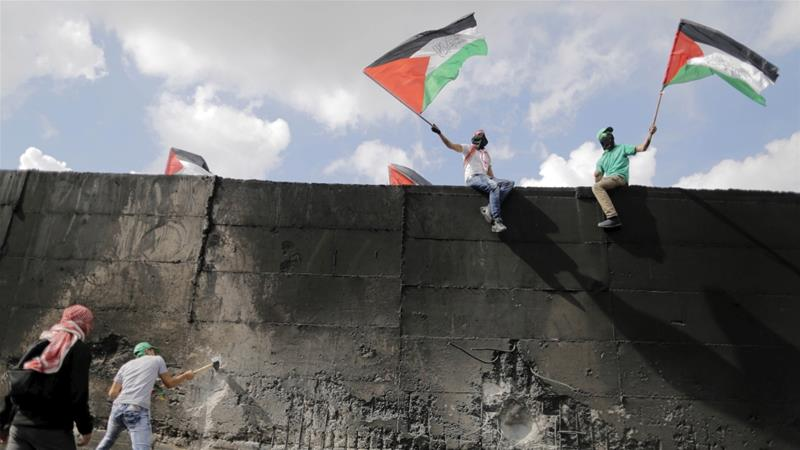A Palestinian protester tries to hammer a hole through the Israeli barrier that separates the West Bank town of Abu Dis from Jerusalem, as others wave Palestinian flags in 2015 [Ammar Awad/Reuters]