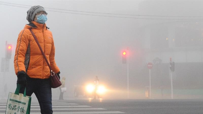 A pedestrian wearing mask walks along a street in heavy smog on December 19, 2016 in Dalian, China. At least 24 cities in North China issued red alerts on Friday as heavy smog will shroud the country''s northern regions in the following two days. [Getty Images]