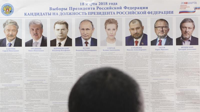 A man stands in front of a broadsheet with information about the candidates at a polling station during preparations for the upcoming presidential election in Russia [Sergey Pivovarov/Reuters]