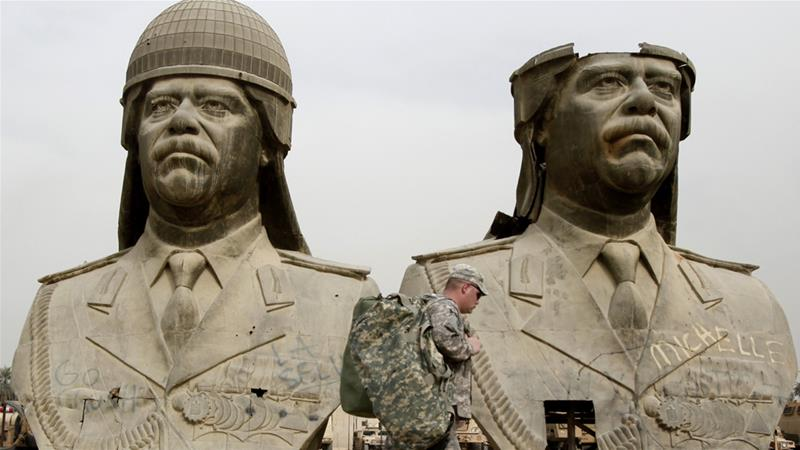 US soldiers stroll past bronze busts of former Iraqi President Saddam Hussein in the Green Zone in Baghdad in 2009 [File: Hadi Mizban/AP]