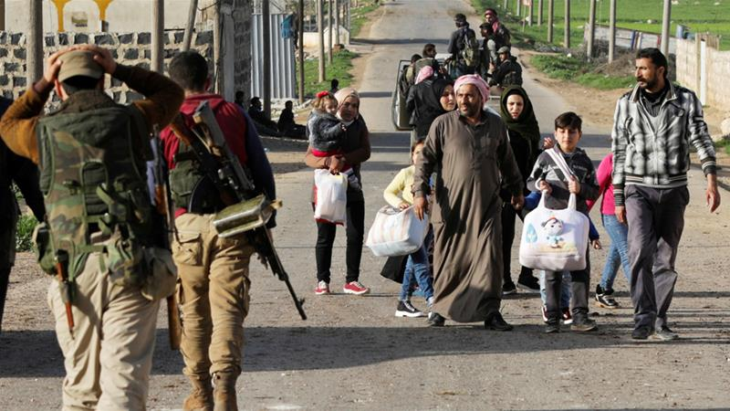 Civilians passed Turkish-backed Syrian fighters as they advanced on Afrin city [Khalil Ashawi/Reuters]