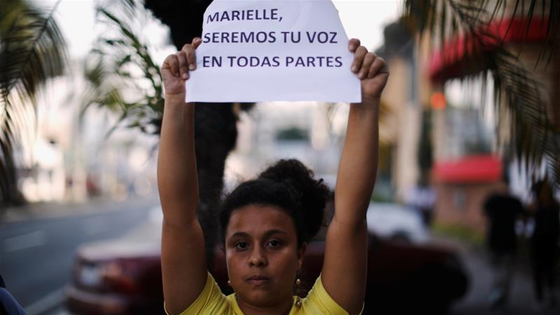 Demonstrators participate in a protest against the murder of Rio de Janeiro City Councilor Marielle Franco. The sign reads: 'Marielle, we will be your voice everywhere' [Jose Cabezas/Reuters]