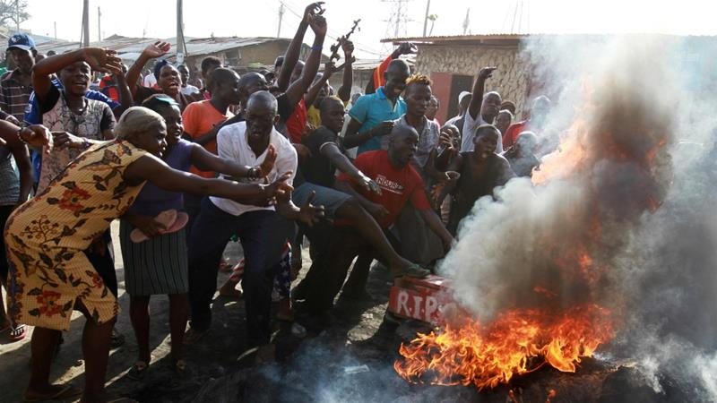 People gesture near tyres set on fire during a protest against a presidential election re-run in Changamwe, Mombasa, Kenya October 26, 2017 [Joseph Okanga/Reuters]