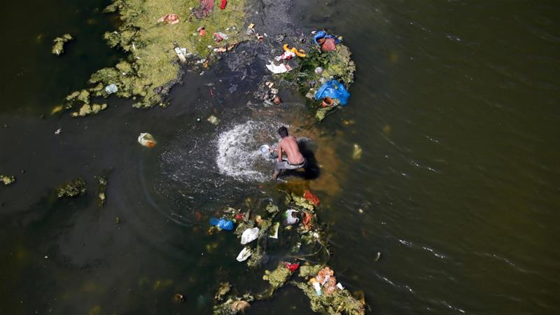 A man looks for recyclable items in the polluted waters of the Sabarmati river, in the face of World Water Day, in Ahmedabad, India, March 21, 2018 [Amit Dave/Reuters]