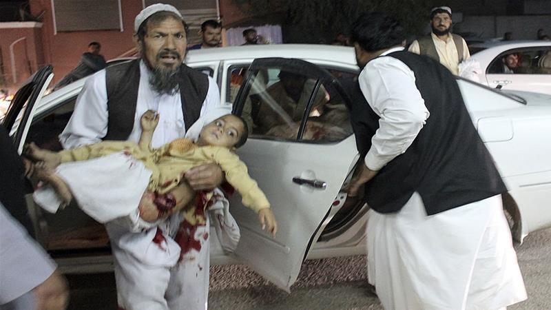 A man carries a wounded boy in a hospital, after a car bombing outside a sports stadium in Lashkar Gah, capital city of southern Helmand province, Afghanistan [Abdul Khaliq/AP]