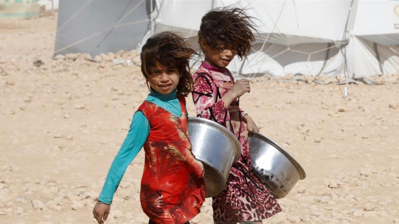Girls carry containers for food rations at a refugee camp in Ain Issa, Syria October 10, 2017 [Erik De Castro/Reuters]