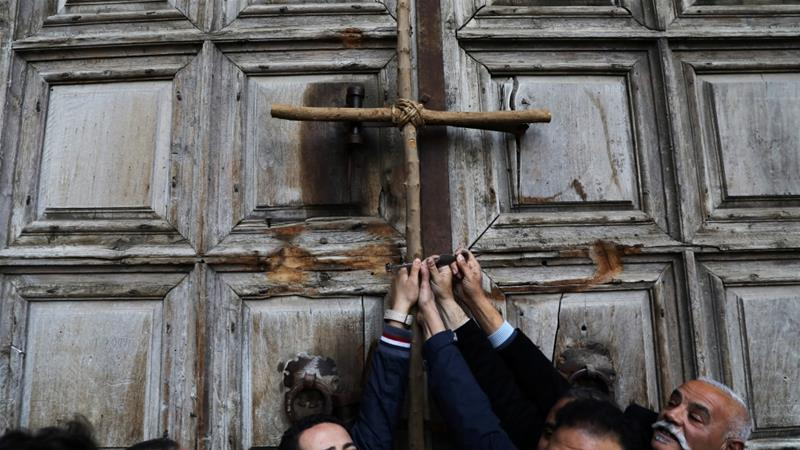 Worshippers hold a cross during a protest in front of the closed doors of the Church of the Holy Sepulchre in Jerusalem''s Old City, February 27, 2018. [Photo/Ammar Awad/Reuters]