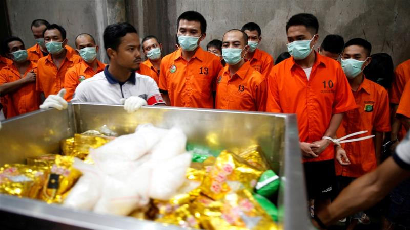 Drug suspects watch as recently confiscated narcotics are wheeled to an incinerator by police following a ceremony by drug enforcement agencies in Jakarta, Indonesia [Darren Whiteside/Reuters]