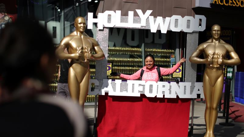 A woman poses for a photo next to golden statues on Hollywood Boulevard near the Dolby Theatre during preparations for the Oscars in Hollywood, Los Angeles, California, US March 1, 2018. [Photo/Lucy Nicholson/Reuters]