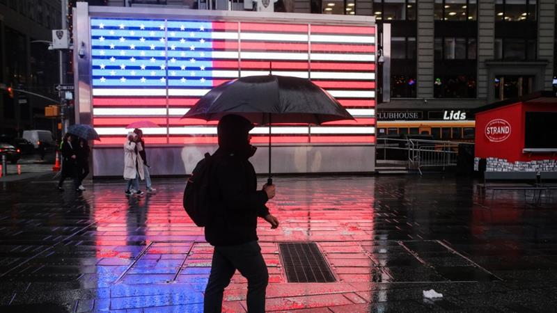A person walks with an umbrella in front of a billboard, displaying a US flag, on a rainy night in New York, United States on March 02, 2018 [Anadolu]