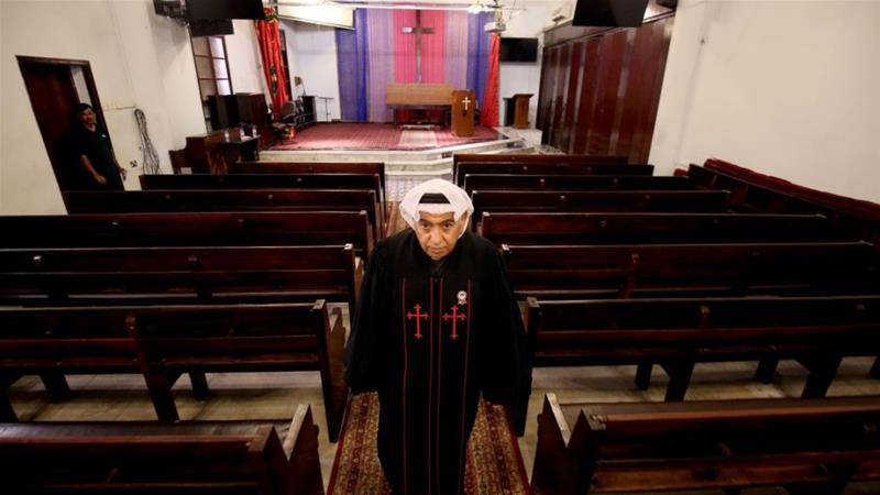 Father Emmanuel Benjamin Jacob Gharib, the first native priest of the Gulf, stands in the aisle of the National Evangelical Church in Kuwait City on February 20, 2018 [Yasser al-Zayyat/AFP]