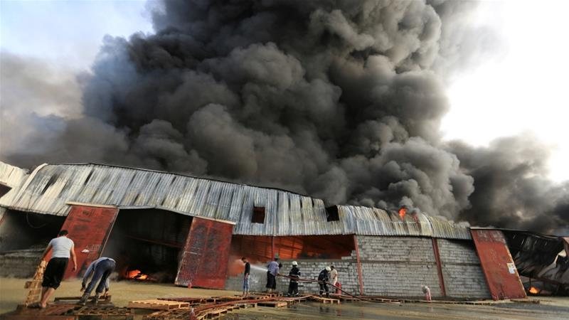 Firefighters try to extinguish a fire engulfing warehouse of the WFP in Hudaida [Abduljabbar Zeyad/Reuters]