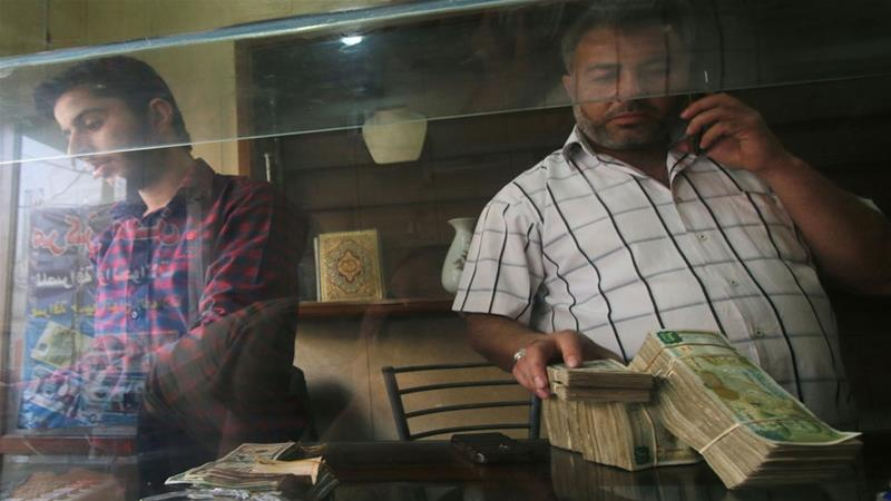 A money exchange vendor holds Syrian currency notes inside his shop in Aleppo [File: Reuters]