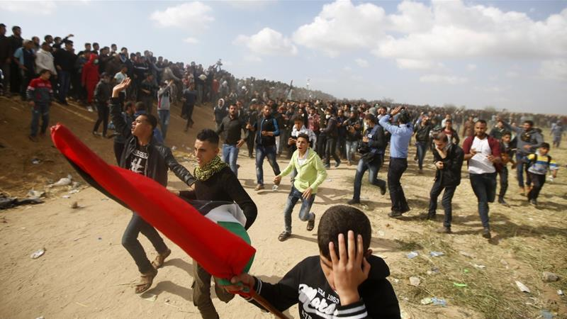 Palestinian protesters react as they evacuate a wounded youth after Israeli troops use live ammunition on protesters in Gaza on Friday, March 30, 2018 [Adel Hana/AP]