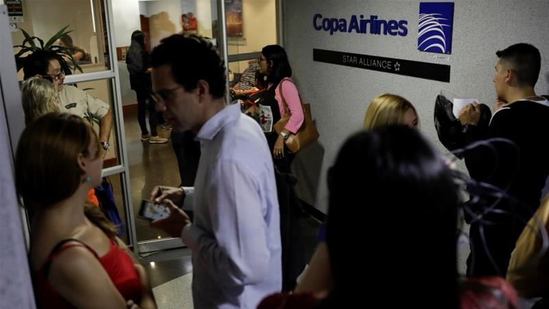 People gather at the gates of Copa Airlines headquarters in Caracas on April 6 [Marco Bello/Reuters]
