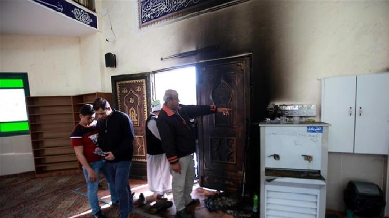 Palestinians inspect damaged Sheikh Sa'ada Mosque after Israeli settlers set its entrance on fire causing some partial damages overnight Thursday, in village of Aqraba, in the occupied West Bank [Nedal Eshtayah/Anadolu]