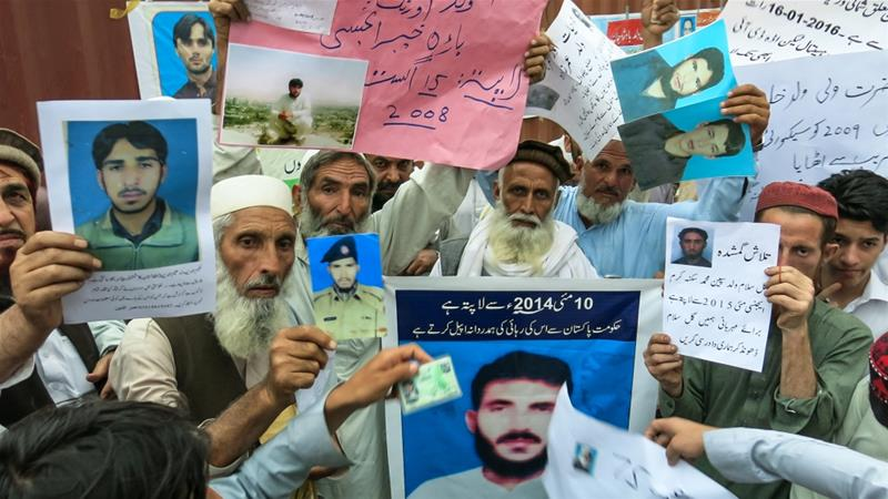 A crowd of people hold aloft banners, posters and photographs of the disappeared people [Asad Hashim/Al Jazeera]