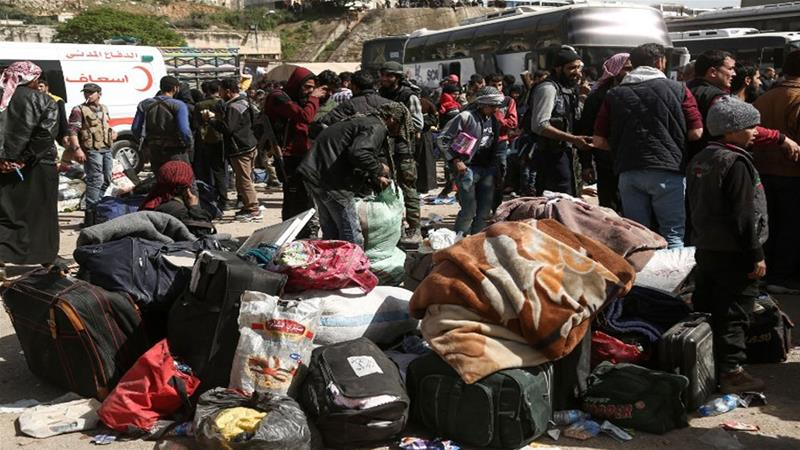 Residents from Eastern Ghouta collect their belongings after they reach the northwest province of Idlib [AFP]