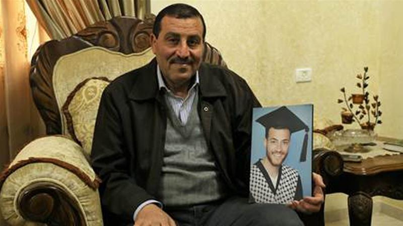 Majed al-Awartani holds of picture of his son Ahmad, who was arrested by the PA over a Facebook post [Yumna Patel/Al Jazeera]