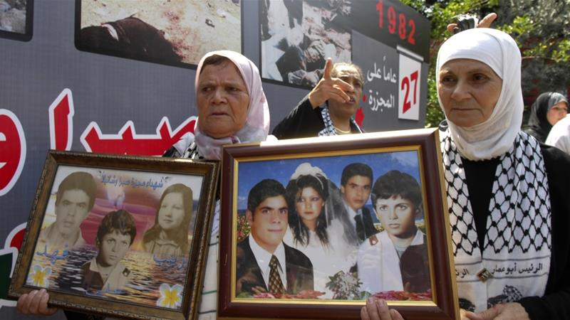 Palestinian women carry pictures of their relatives who were killed during Sabra and Shatila massacre at the mass graves in Beirut on September 18, 2009 [Ahmad Omar/AP Photo]