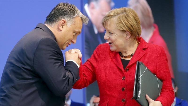 Hungary's Prime Minister Viktor Orban kisses the hand of German Chancellor Angela Merkel as they attend a European People's Party congress in Madrid on October 22, 2015 [Andrea Comas/Reuters]